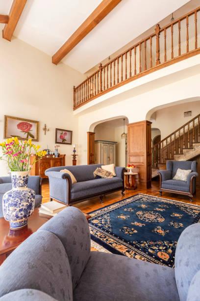 echtes foto von einem wohnzimmer interieur mit blauem sofa, teppich, porzellanvase mit blumen und treppen - teppich englisch stock-fotos und bilder