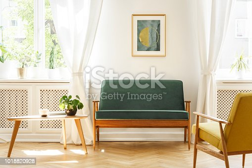 Real photo of a mid-century living room interior with a sofa, coffee table, windows and painting