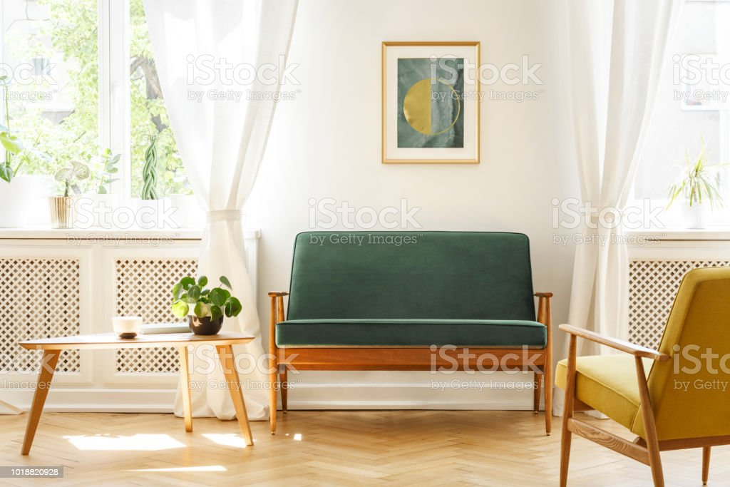 Real photo of a mid-century living room interior with a sofa, coffee table, windows and painting stock photo