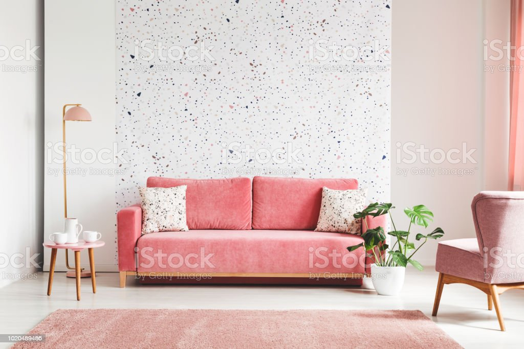 Real photo of a pink, velvet sofa, plant, coffee table with pot and cups on a lastrico wall in a living room interior – zdjęcie