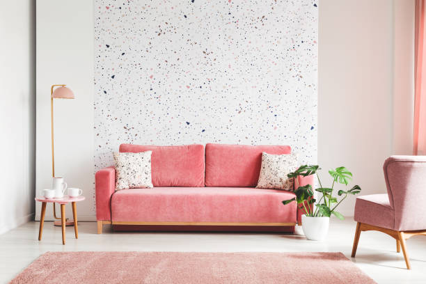Real photo of a pink, velvet sofa, plant, coffee table with pot and cups on a lastrico wall in a living room interior stock photo