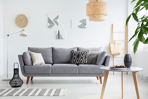 Real photo of a scandi living room interior with cushions on gray couch, cherries on wooden table and bag on a ladder