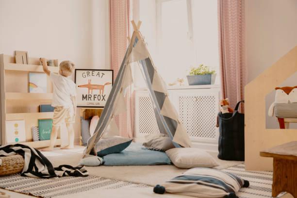 echtes foto eines scandi spielzimmer-interieur mit einem zelt und kissen. junge stellen ein spielzeug auf ein regal - fuchs kissen stock-fotos und bilder
