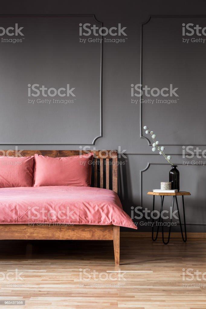 Photo réelle d'un lit simple et élégant avec une literie rose sale à côté d'un tabouret de bois dans l'intérieur de la chambre à coucher avec mur foncé - Photo de Ameublement libre de droits