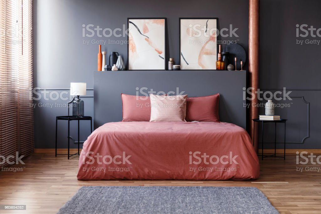 Real photo of a simple bedroom interior with dirty pink bedding on the bed standing against dark gray wall with molding, between two, metal bedside tables - Royalty-free Apartment Stock Photo