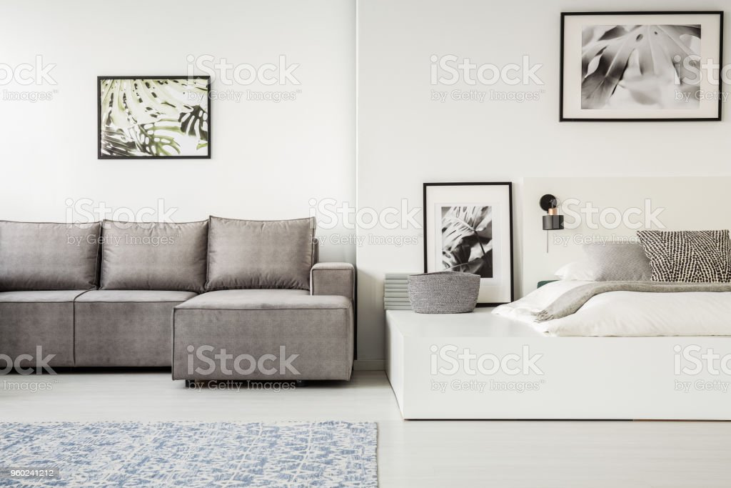Real photo of a simple, open space flat interior with sleeping and living space. Gray corner sofa next to a white bed on a platform stock photo