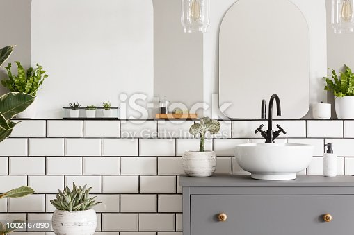Real photo of a sink on a cupbaord in a bathroom interior with tiles, mirror and plants