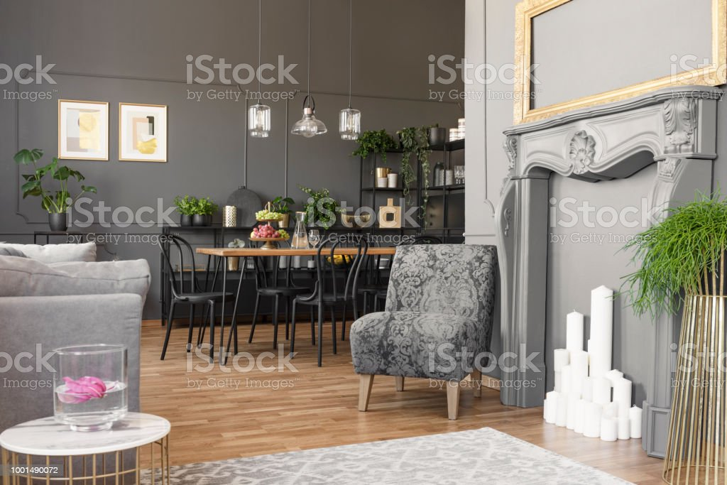 Real photo of a spacious and elegant living room interior with golden frame above a faux fireplace standing next to an armchair with vintage pattern stock photo