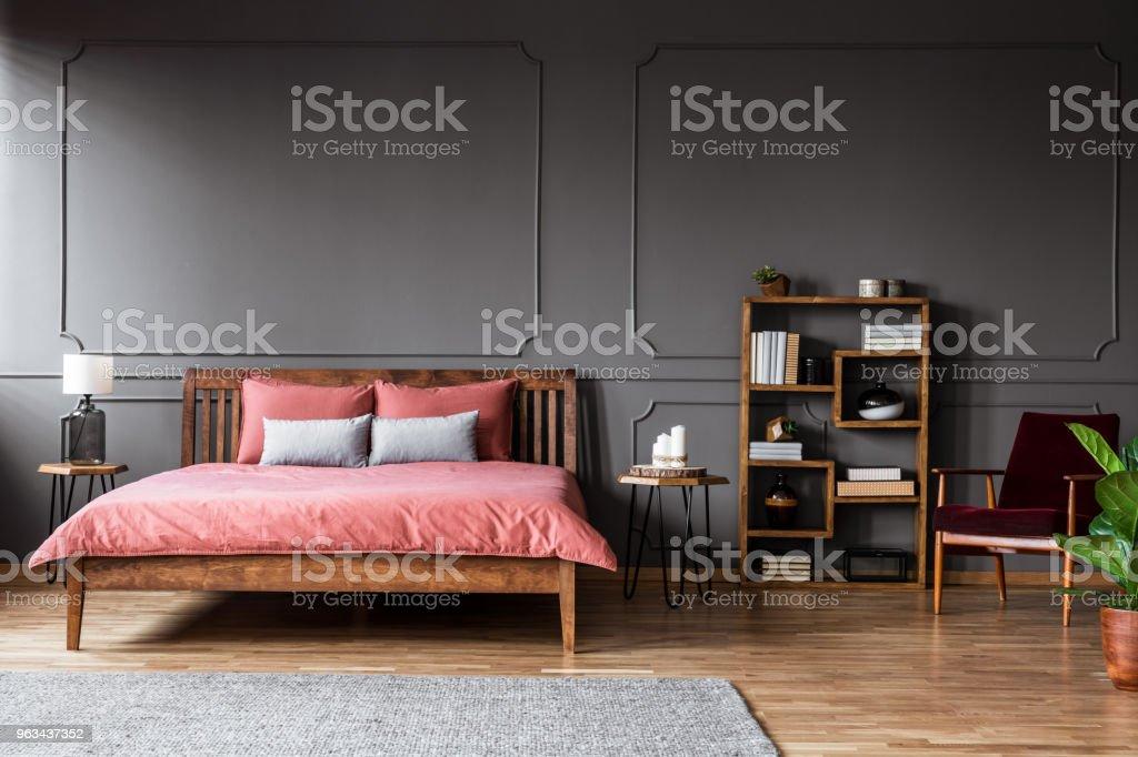 Photo réelle d'un intérieur de chambre à coucher spacieuse avec pied de lit rose contre un mur noir avec le bâti à côté une étagère créatif et fauteuil rouge - Photo de Ameublement libre de droits