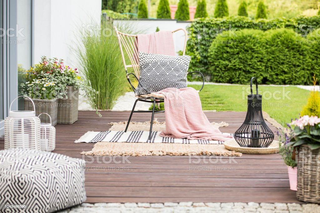 Real photo of a white pillow and pink blanket on a rattan chair standing in the garden of a luxurious house stock photo