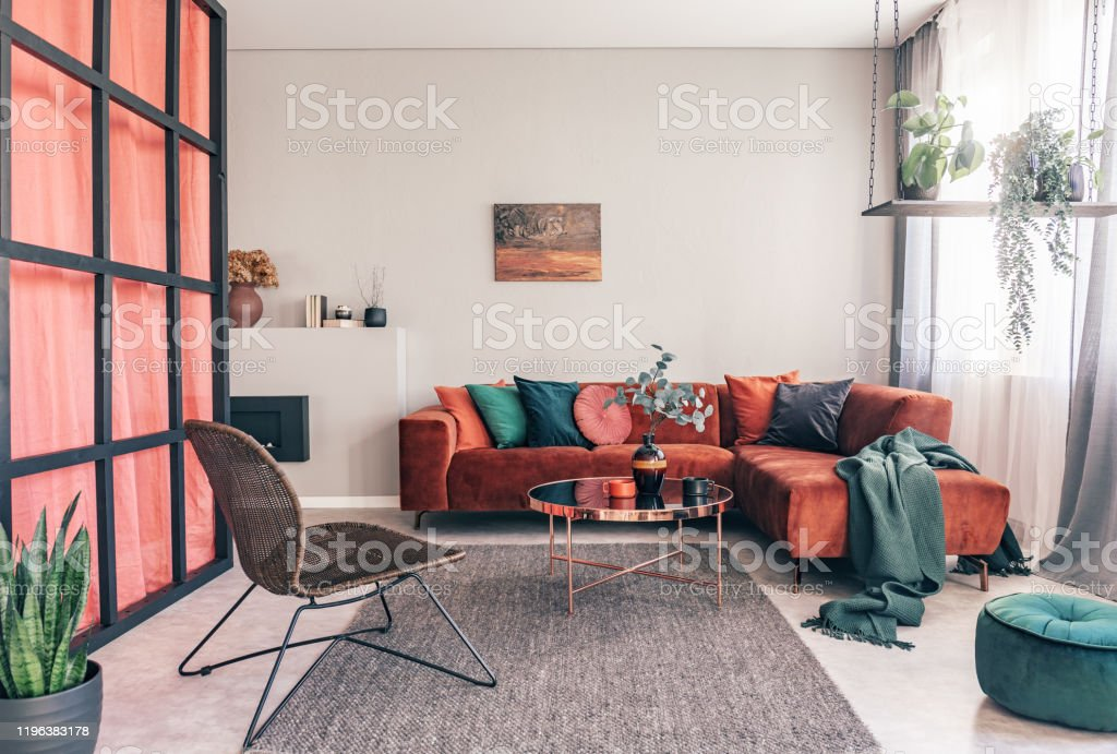 Real Photo Of A Wicker Chair Gray Rug And Red Corner Couch In Colorful Living Room Interior With Green Accents Stock Photo Download Image Now Istock