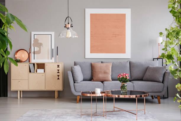echtes foto von einem hölzernen schrank neben einem sofa in einem modernen wohnzimmer interieur mit einem großen gemälde - dekoleuchten stock-fotos und bilder