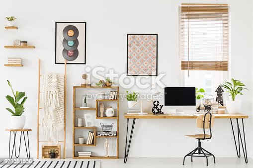 istock Real photo of a workplace interior with a computer on a desk next to a chair and a shelf with ornaments, posters on a wall and a window with blinds 971381536
