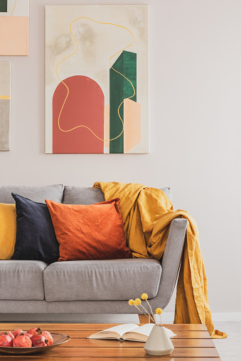 Real photo of an abstract painting hanging on white wall in living room interior with colorful cushions on gray sofa