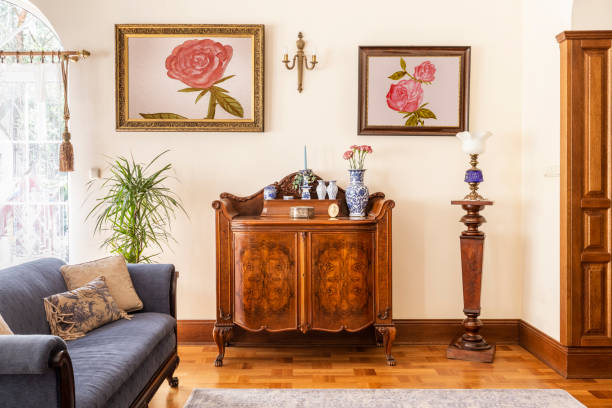 Real photo of an antique cabinet with porcelain decorations, paintings with roses and blue sofa in a living room interior Real photo of an antique cabinet with porcelain decorations, paintings with roses and blue sofa in a living room interior antique stock pictures, royalty-free photos & images