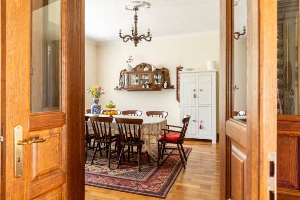 echtes foto der innenansicht antikes esszimmer mit großem tisch, stühlen, wandschrank und teppich. blick durch eine tür - teppich englisch stock-fotos und bilder