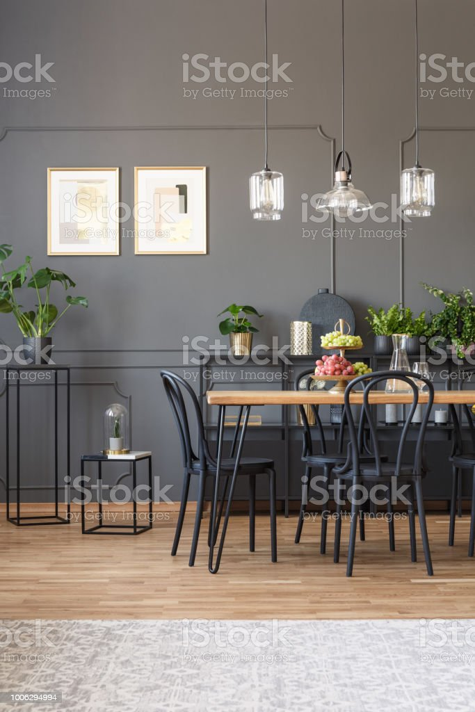 Real photo of an elegant dining room interior with molding on dark wall, black chairs at a wooden table and glass lamps stock photo