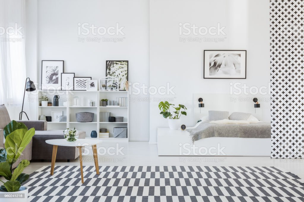 Real photo of an open space apartment interior with a cozy gray bed on a white platform and a wooden table next to a sofa stock photo