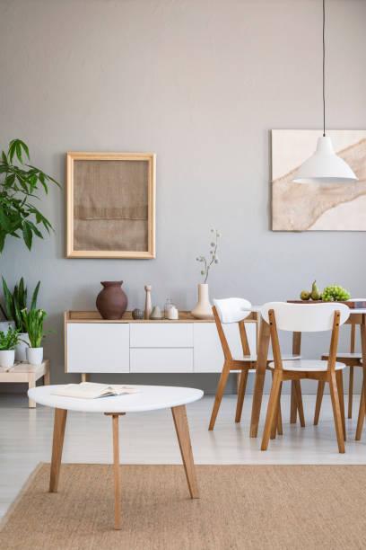 echtes foto von einer freifläche speisesaal mit holztisch und stühle neben einem einfachen schrank und tisch auf einem natürlichen teppich - sideboard skandinavisch stock-fotos und bilder