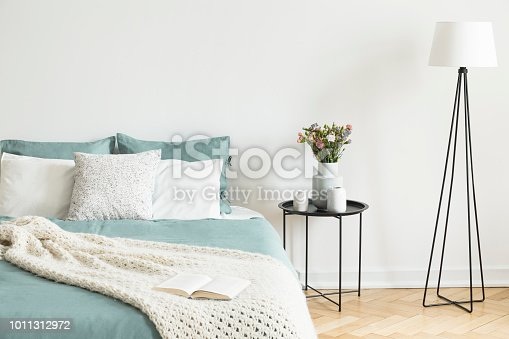 Real photo of bright bedroom interior with fresh flowers on bedside table, metal lamp and open book placed on bed with pastel bedding and knit blanket