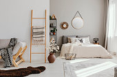 Real photo of bright open space bedroom interior with window with curtains, mirror and clock on the wall, ladder with blanket, carpet and fluffy rug on the floor and king-size bed with pillows