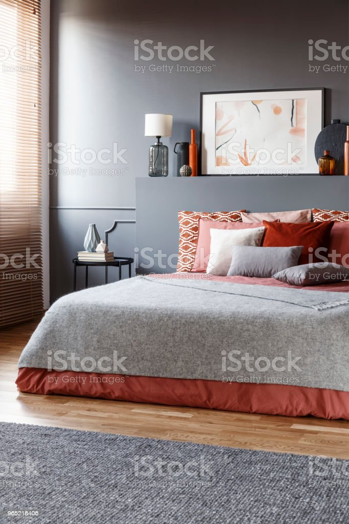 Real photo of dark, elegant bedroom interior with black walls, lamp and poster on the bedhead behind bed with gray blanket and cushions zbiór zdjęć royalty-free