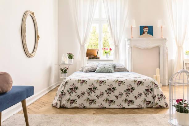 echtes foto von englischen interieur schlafzimmer mit kingsize-bett, fenster mit vorhängen, fischgrät-parkett und faux kamin - teppich englisch stock-fotos und bilder