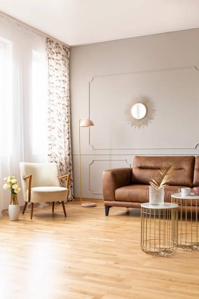 echtes foto von voller täglichen lichtraum mit retro-sessel, lampe, braune ledercouch und stilvolle tabellen - ledersessel braun stock-fotos und bilder