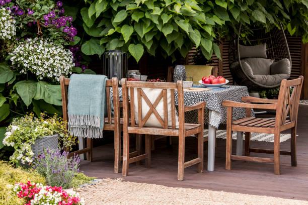 echtes foto von gartenmöbel auf der terrasse voller blumen und pflanzen - veranda decke stock-fotos und bilder