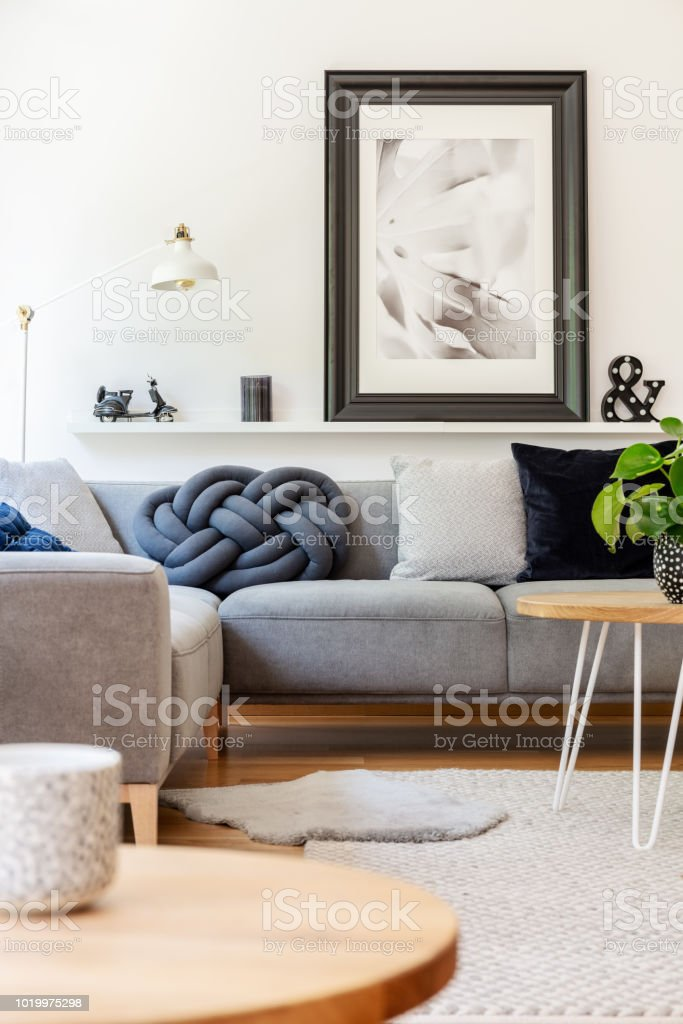 Real Photo Of Handmade Knot Pillow Placed On Grey Corner Sofa Standing In White Living Room Interior With Lamp Decor And Poster On Shelf Stock Photo Download Image Now Istock