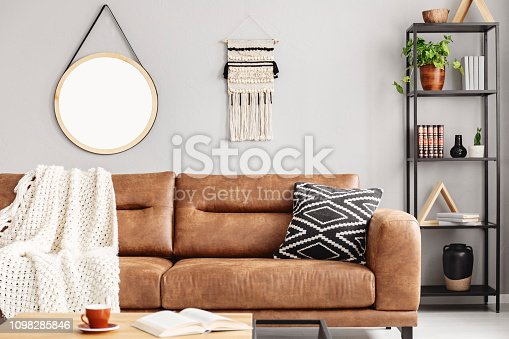 istock Real photo of handmade macrame and mockup poster hanging on the wall in bright sitting room interior with leather sofa and metal rack with decor and books 1098285846