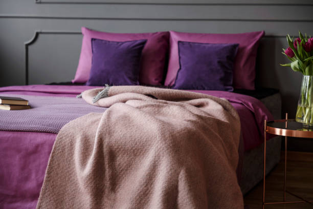 echtes foto von modernen hotel schlafzimmer innenraum mit rosa decke auf - pflaumen wände stock-fotos und bilder