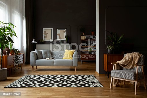 Real photo of open space dark living room interior with molding and posters on wall, patterned carpet, lounge with cushions and retro furniture