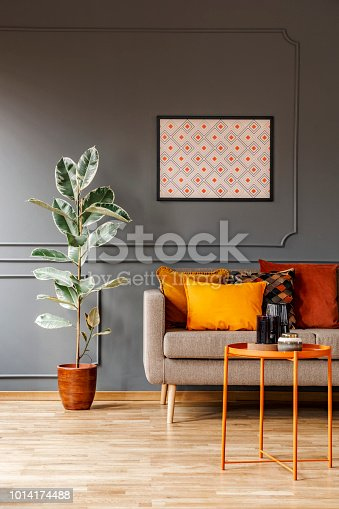 Real photo of poster with geometric pattern hanging on the wall with wainscoting in dark living room interior with fresh plant, sofa with cushions and metal end table with decor