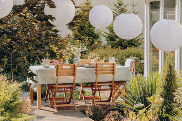 real photo of round lamps above a table with wooden chairs in a garden - home decor boho imagens e fotografias de stock