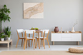 Real photo of Scandi dining room interior with vases on cupboard, chairs standing by the table with fresh fruits, poster with textile hanging on wall and plants placed on wooden platform