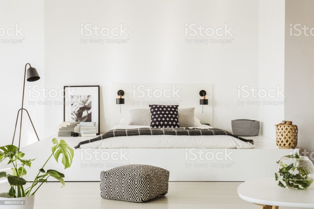 Real photo of spacious, scandi bedroom interior with patterned pouf in front of a bed on a platform with dark blanket and decorative cushions stock photo