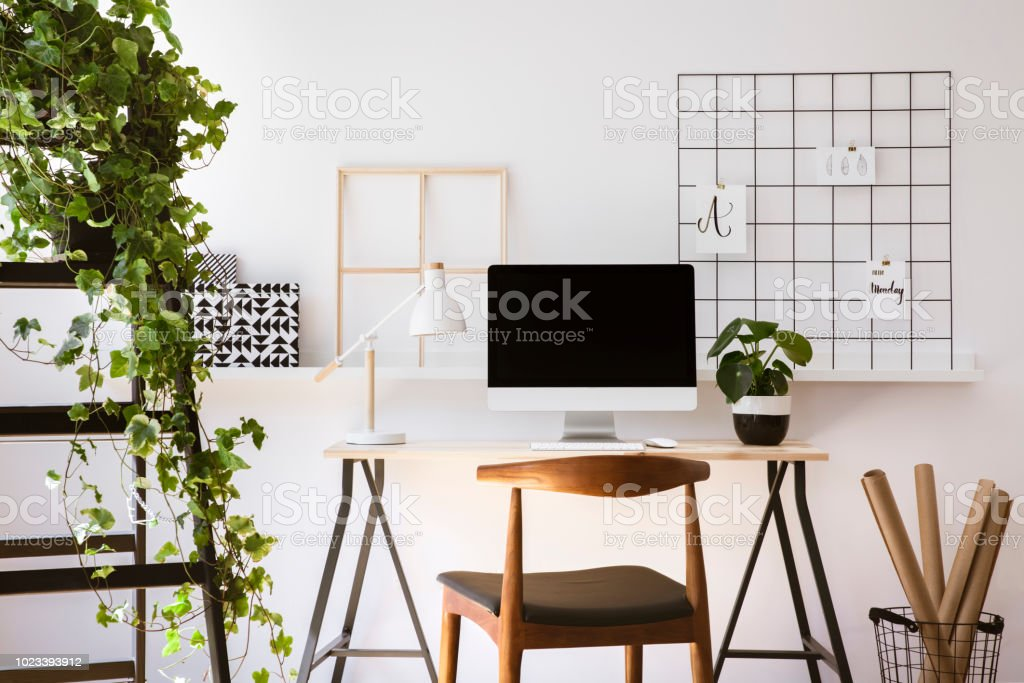 Real photo of wooden desk with metal lamp, fresh plant and empty...