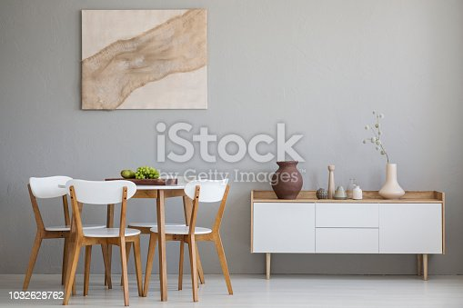 Real photo of wooden table and four chairs standing in light grey dining room interior with modern art poster and cupboard with decor