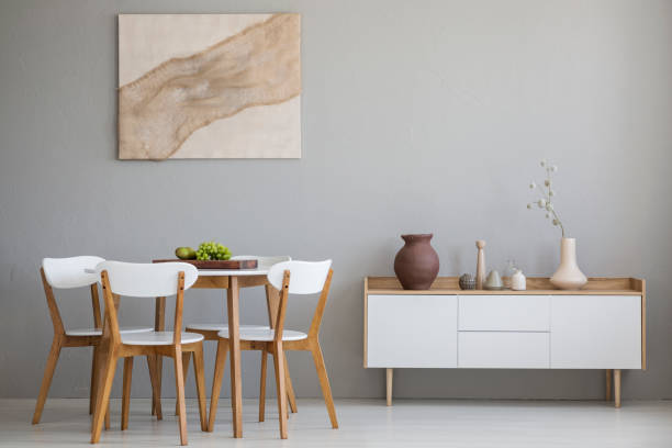 Real photo of wooden table and four chairs standing in light grey dining room interior with modern art poster and cupboard with decor stock photo