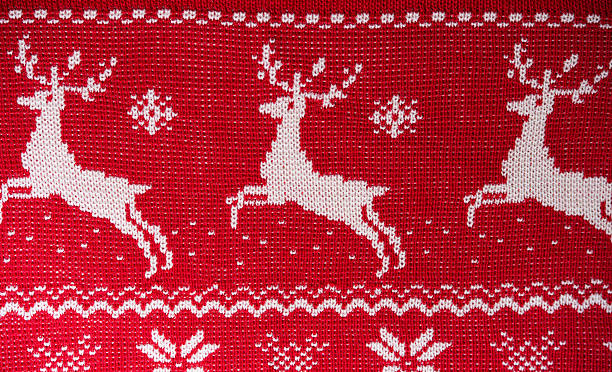 real red knitted background with white christmas reindeer - animal markings stock photos and pictures