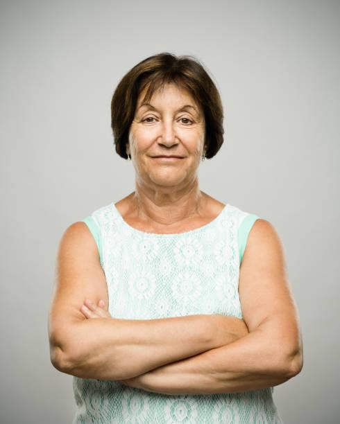 echt ontspannen senior vrouw portret met gekruiste armen - zuid europese etniciteit stockfoto's en -beelden
