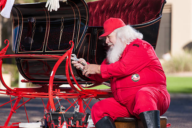 Real Santa Fixing His Sleigh Real Santa Fixing His Sleigh flight suit stock pictures, royalty-free photos & images