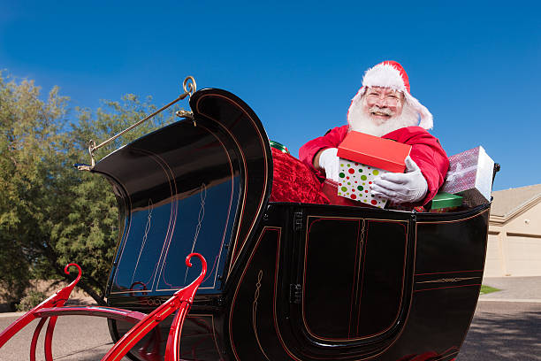 Real Santa in Sleigh Handing Out Gifts Real Santa in Sleigh Handing Out Gifts flight suit stock pictures, royalty-free photos & images