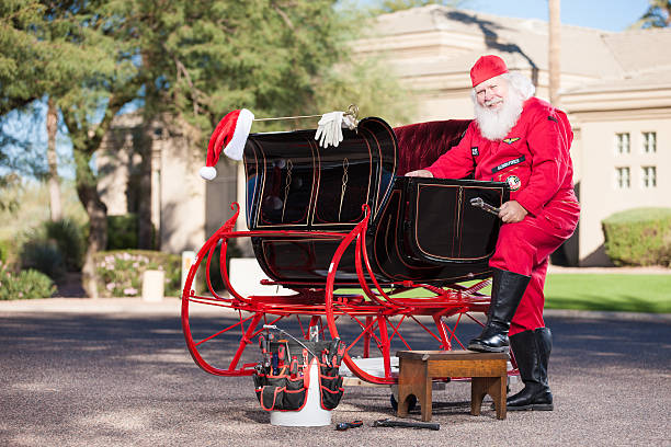 Real Santa Mechanic Working on Sleigh Real Santa Mechanic Working on Sleigh flight suit stock pictures, royalty-free photos & images
