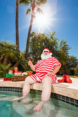 Real Santa Claus on vacation relaxing during the summer months by the swimming pool.