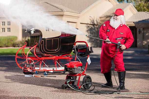 Real Santa Washing His Sleigh Real Santa Washing His Sleigh Down with a Power Washer Sprayer flight suit stock pictures, royalty-free photos & images