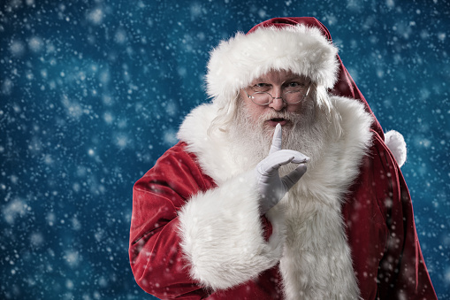 Sshhhh. Santa stands outside in the falling snow with his finger to his lips, telling you to be quiet and keep his secret.