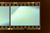 Real scan of old 35mm filmstrip or photo frame with burned edges on dark background