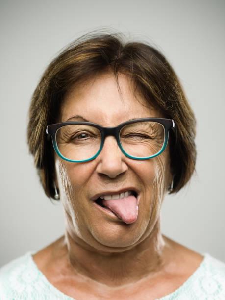 echte senior frau porträt die zunge heraus - menschlicher mund stock-fotos und bilder